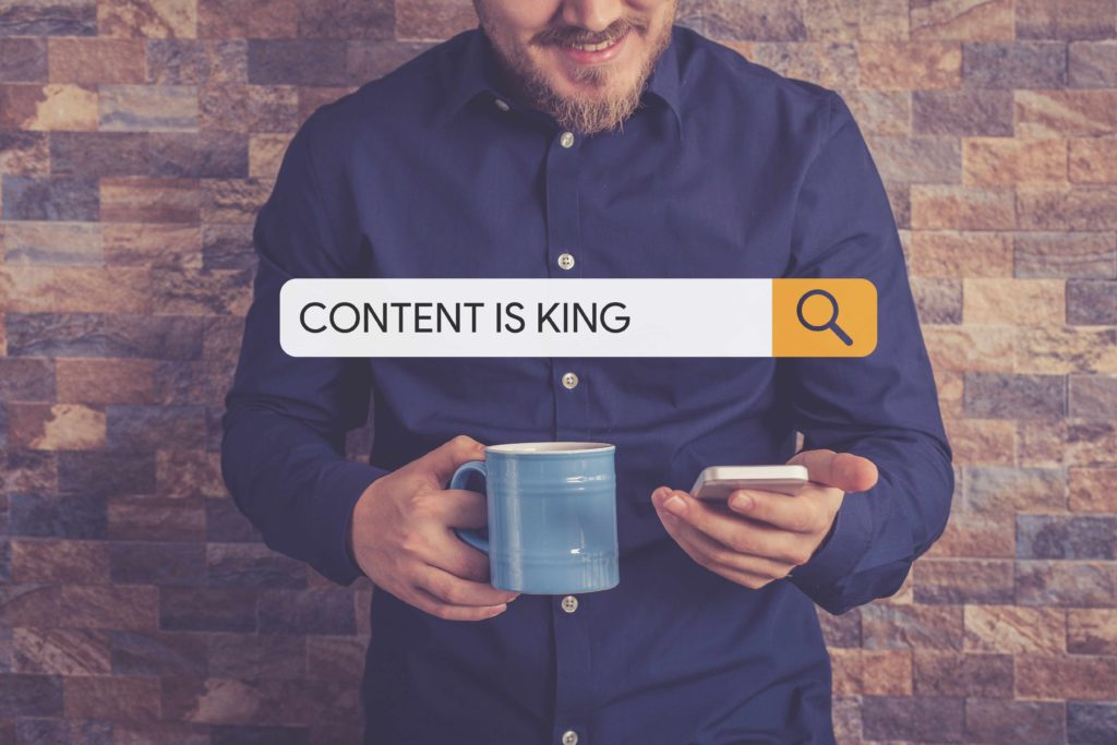 Content syndication. Content is king - inscription in search field. Man stay near brick wall with phone and coffee cup and smiling