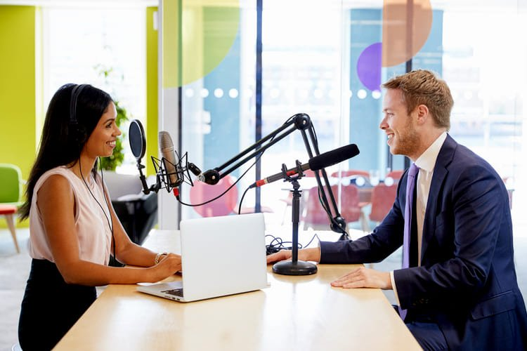 Young woman interviewing a guest in a studio for a podcast GRINFER