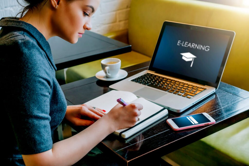 Businesswoman sitting at table in cafe in front of laptop with inscription on screen e-learning GRINFER