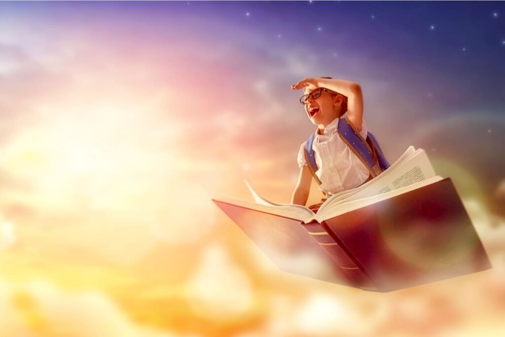 Child flying on the book on background of sunset sky