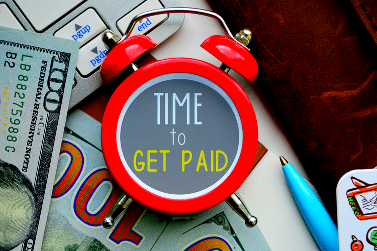 Time to get paid-sign on red clock with cash