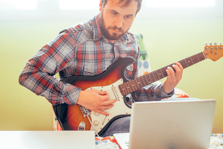 Man concentrating as he learns to play the guitar thanks to a tutorial on his laptop at home