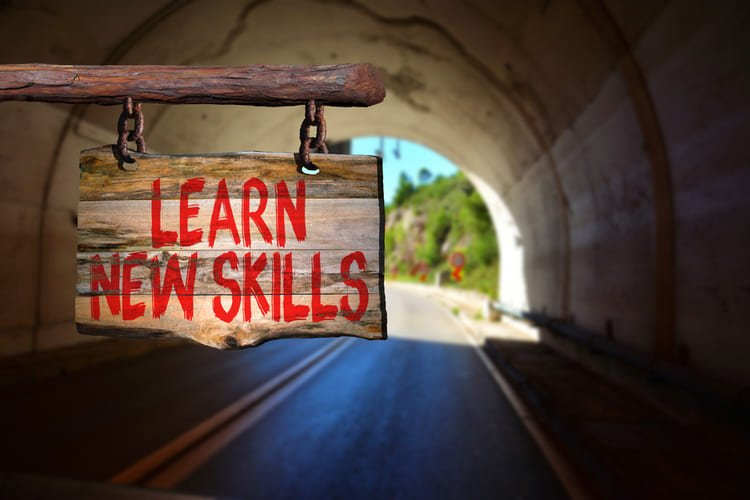 Learn new skills motivational phrase sign on old wood with blurred background