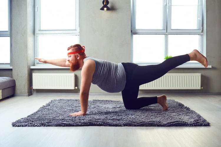 A funny fat bearded man in sports clothes does yoga in the room