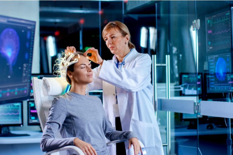 Woman Wearing Brainwave Scanning Headset Sits in a Chair while Scientist Adjusts the Device, Looks at Displays