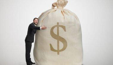 happy man embracing big bag with money