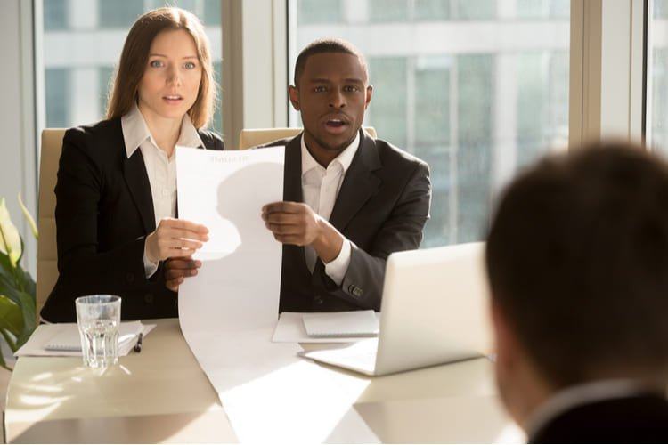 recruiters holding long sheet of paper looking surprisingly at candidate during job interview